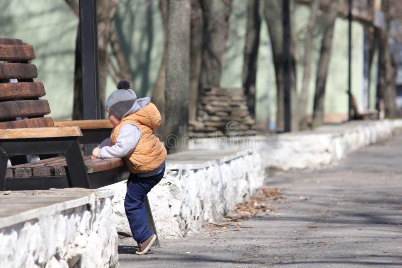 Nettes Kind, das im Frühjahr auf dem Park der Bank klettert stockfotografie