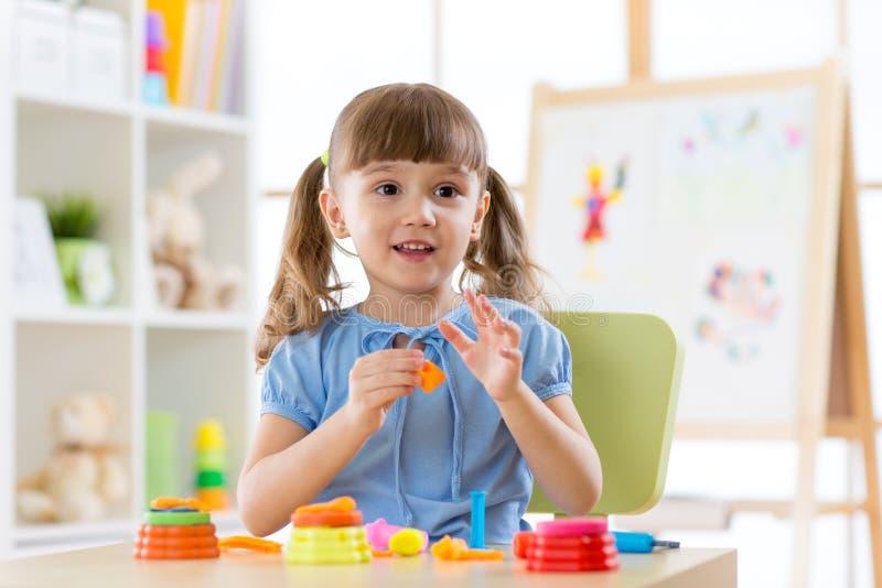 Nettes Kind, das mit sculpting Spielzeug im Kindertagesstätte spielt Kleines Mädchen mit Plasticine lizenzfreie stockfotos