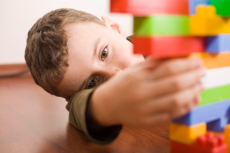 Nettes Kind, das mit Würfeln spielt stockbild