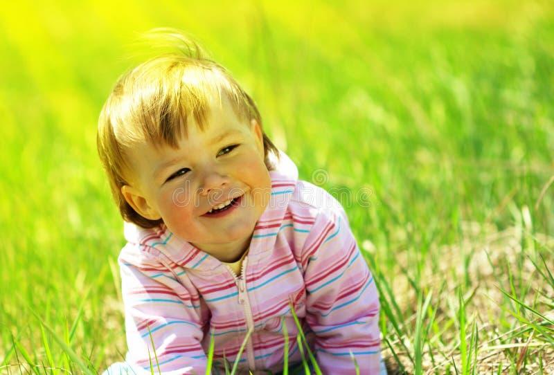 Nettes Kind, das Spaß auf der Wiese hat stockfotos