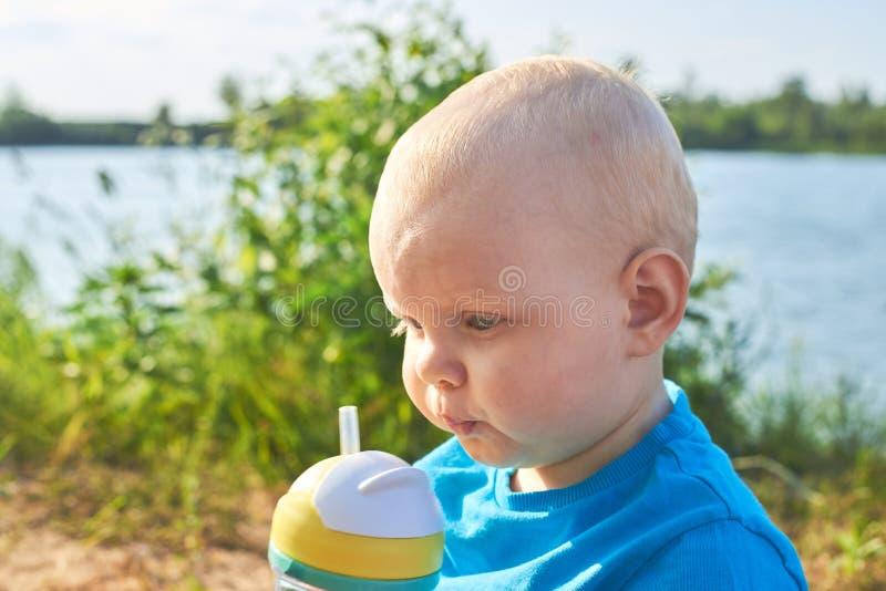 Nettes Kind, das von einer Flasche mit einem Stroh auf der Flussbank an einem heißen Sommertag trinkt lizenzfreies stockfoto