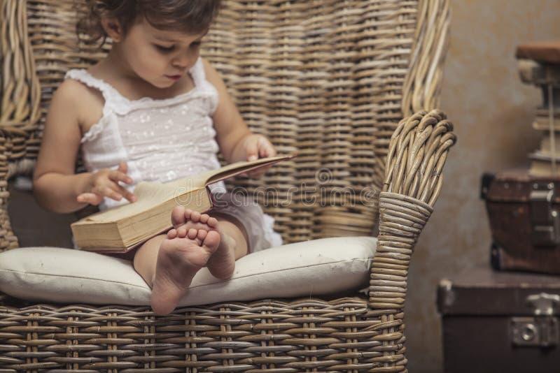 Nettes Kind des kleinen Mädchens in einem Stuhl, ein Buch im Innenraum lesend stockbild