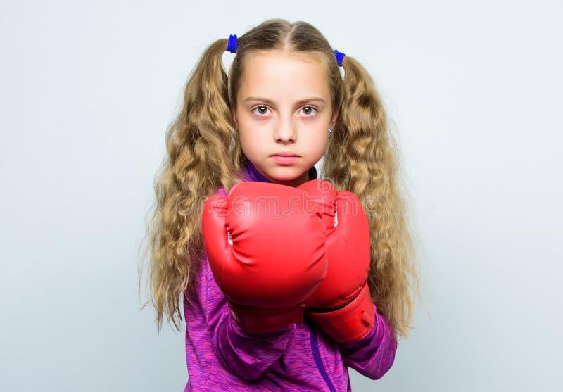 Nettes Kind des Mädchens mit den roten Handschuhen, die auf weißem Hintergrund aufwerfen Nettes Kind mit Sportboxhandschuhen Boxe lizenzfreie stockfotos