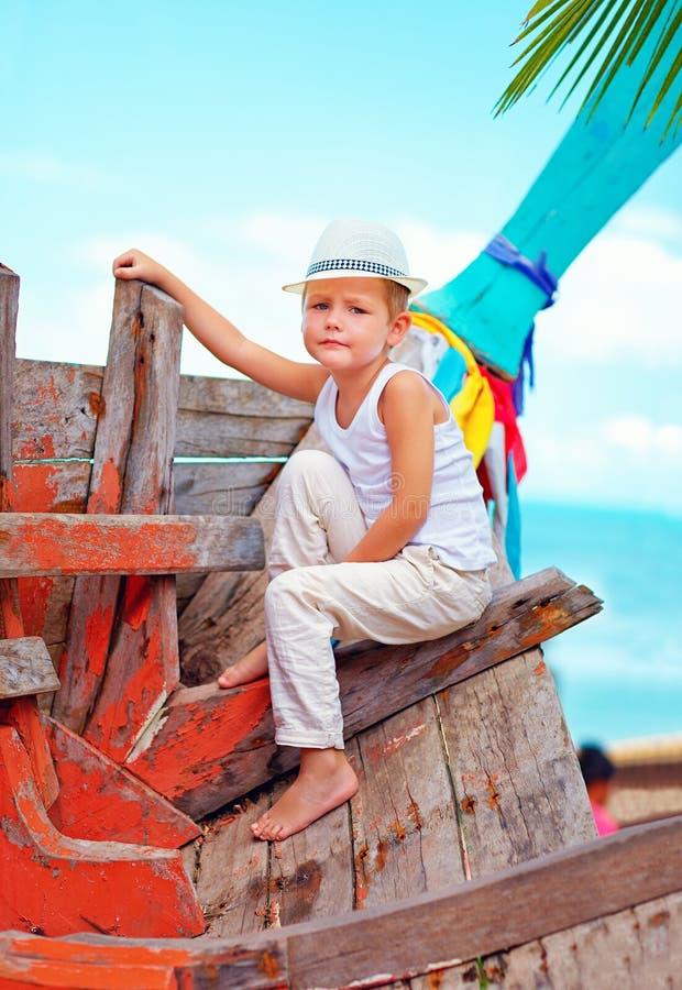 Nettes Kind, Junge, der auf altem Boot auf tropischem Strand sitzt lizenzfreie stockfotografie