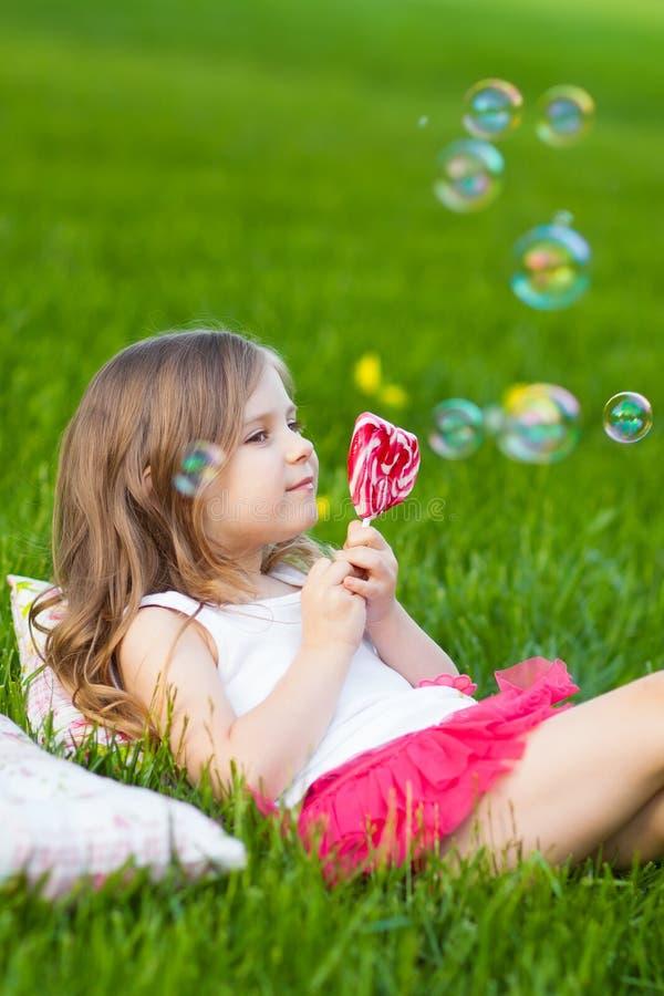 Nettes Kind mit dem Lutscher, der auf dem Gras stillsteht lizenzfreie stockbilder