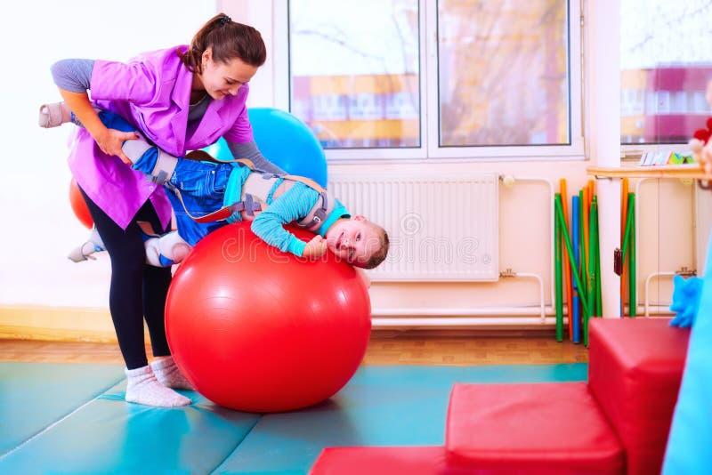 Nettes Kind mit Unfähigkeit hat musculoskeletal Therapie, indem er Übungen in den Körperfestlegungsgurten auf Sitzball tut stockfotos