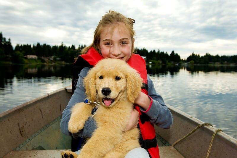 Nettes Kind und ein Welpe auf einem See lizenzfreie stockfotos