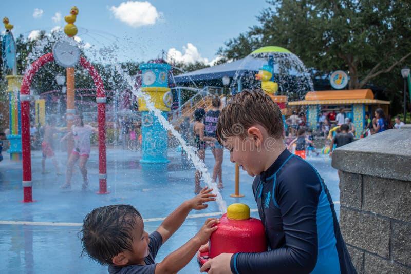 Nettes Kind und kleiner Junge, die mit dem Wasserstrahl im Sesame Street-Bereich bei Seaworld 2 spielt stockbilder