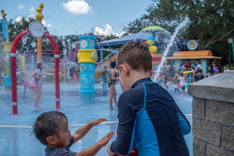 Nettes Kind und kleiner Junge, die mit dem Wasserstrahl im Sesame Street-Bereich bei Seaworld 3 spielt lizenzfreie stockfotos