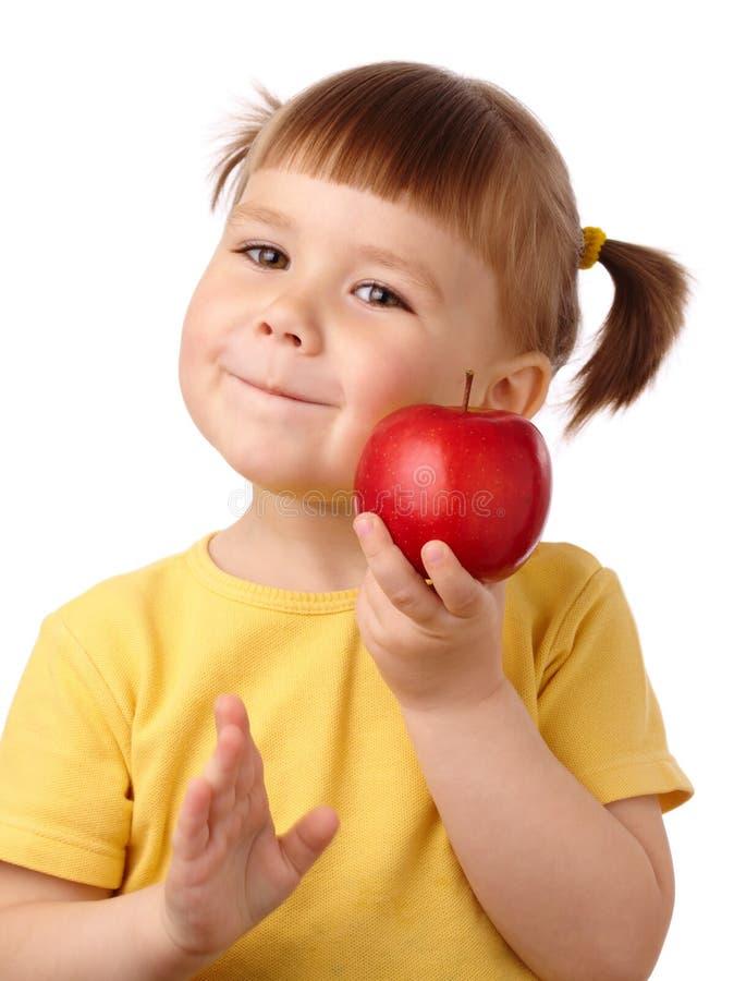 Nettes Kind wird einen Apfel beißen stockfotos