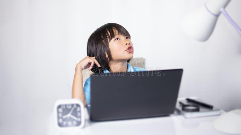 Nettes Kinderdenkender und Schreibenlaptop stockfotos