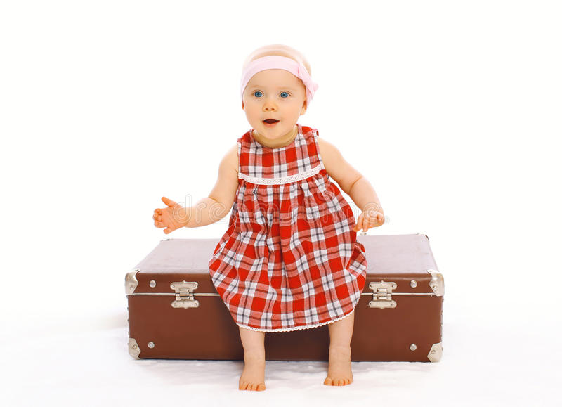 Nettes Kinderkleines Mädchen im Kleid, das auf dem Kofferspielen sitzt lizenzfreie stockfotografie