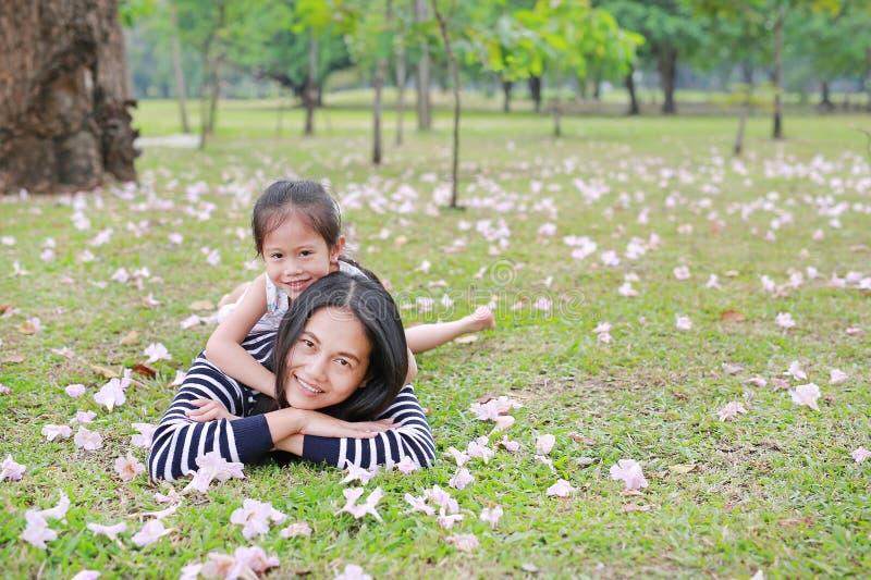 Nettes Kinderm?dchen streicheln ihre Mutter, die v?llig auf gr?nem Feld mit Fallrosablume im Garten im Freienliegt Gl?ckliche lie stockfotografie