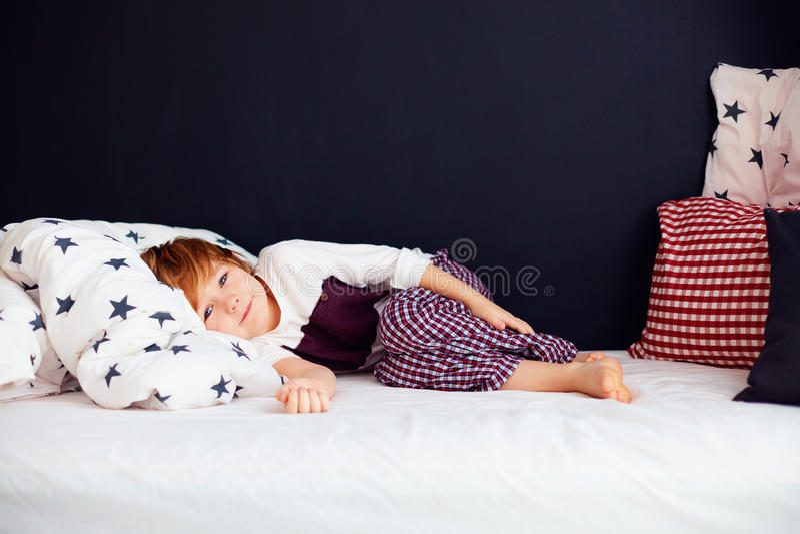 Nettes Kindertragende Pyjamas, entspannter Junge, der im Bett liegt lizenzfreie stockbilder