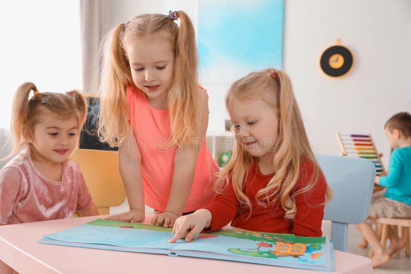 Nettes kleine Kinderlesebuch zusammen bei Tisch zuhause lizenzfreies stockbild