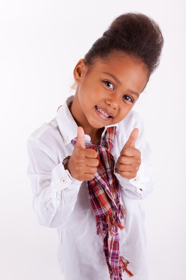Nettes kleines afrikanisches asiatisches Mädchen, das Daumen bildet stockbilder