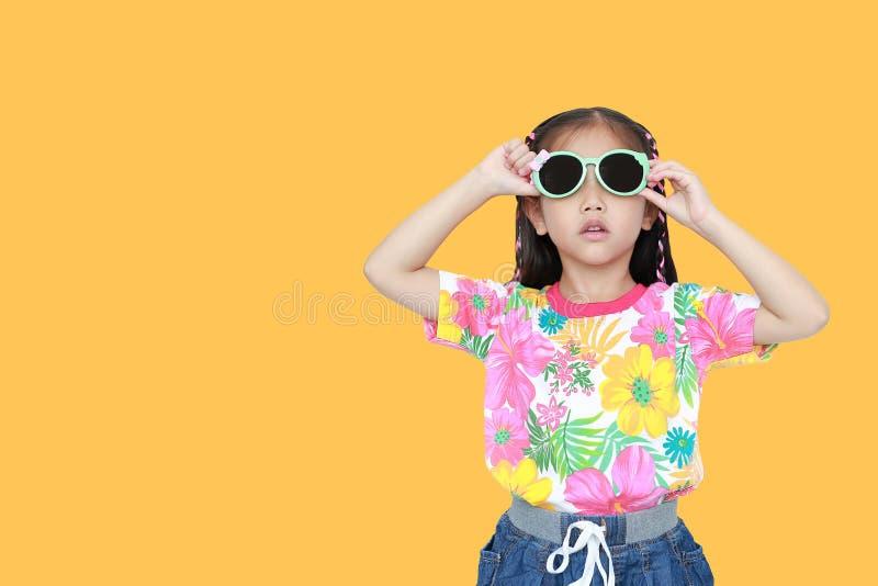Nettes kleines asiatisches Kindermädchen, das ein Blumensommerkleid und -Sonnenbrille lokalisiert auf gelbem Hintergrund mit Kopi stockfotos