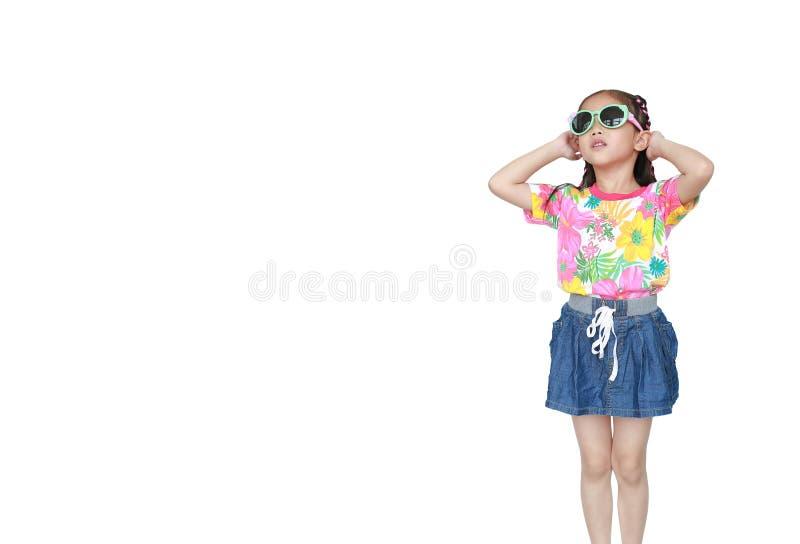 Nettes kleines asiatisches Kindermädchen, das ein Blumensommerkleid und -Sonnenbrille lokalisiert auf weißem Hintergrund trägt Be stockbild
