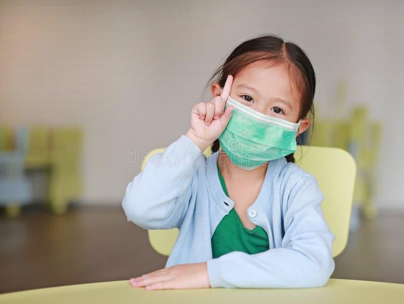 Nettes kleines asiatisches Kindermädchen, das eine Schutzmaske mit dem Zeigefinger der Vertretung eine sitzt auf Kinderstuhl im K stockbild