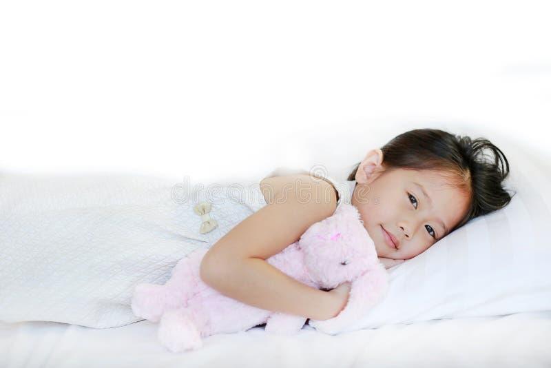 Nettes kleines asiatisches Mädchen, das auf Bett liegt und eine Puppe streichelt stockfotografie