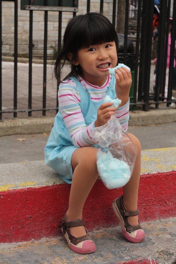 Nettes kleines asiatisches Mädchen, das Zuckerwatte isst stockbilder
