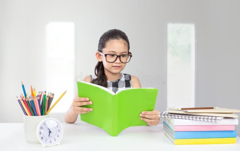 Nettes kleines asiatisches Mädchenabnutzungsglas-Lesebuch lizenzfreie stockbilder