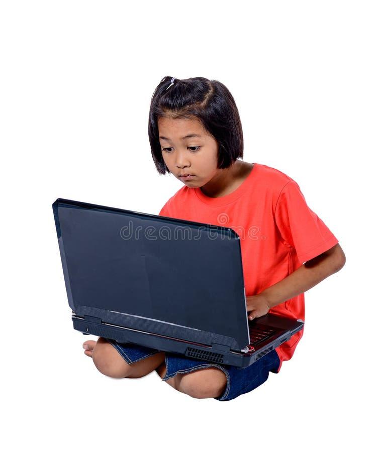 Nettes kleines asiatisches Mädchenkind, das auf dem Boden studiert oder verwendet den Laptop lokalisiert auf weißem Hintergrund s lizenzfreies stockbild