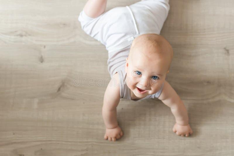 Nettes kleines Baby, das auf Hartholz und dem Lächeln liegt Kind, das über hölzernes Parkett kriecht und oben mit glücklichem Ges lizenzfreies stockbild