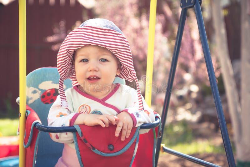 Nettes kleines Baby, das auf Schwingen während des sonnigen Sommertages im Park sitzt lizenzfreie stockfotos