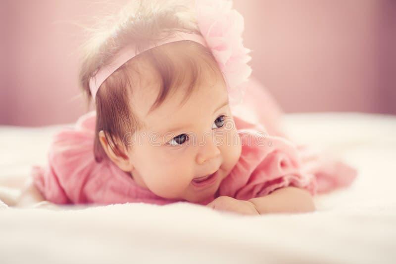 Nettes kleines Baby, das im Bett im rosa Kleid liegt lizenzfreies stockbild