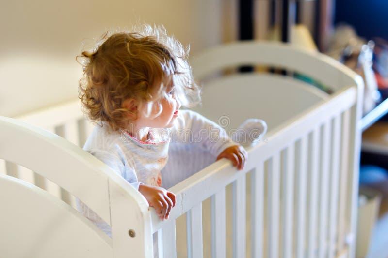 Nettes kleines Baby, das im Feldbett nachdem dem Schlafen liegt Gesundes glückliches Kind im Bett, das heraus klettert lizenzfreies stockfoto