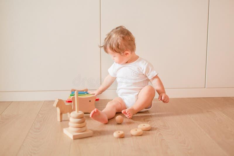 Nettes kleines Baby, das mit dem Stapeln von Ringen spielt stockbild