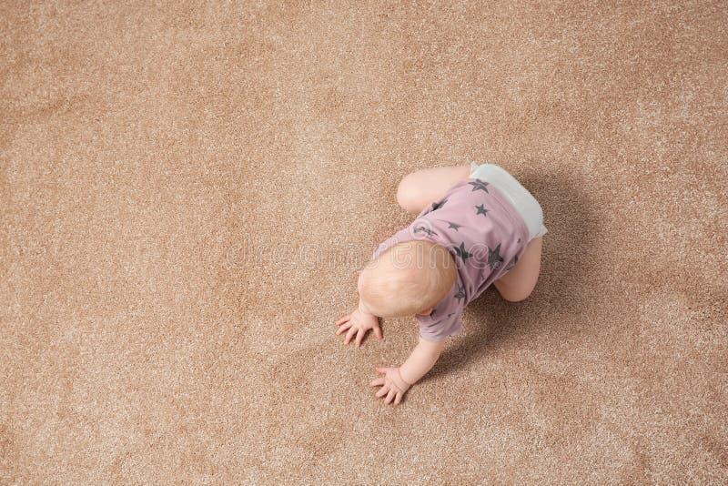 Nettes kleines Baby, das zuhause auf Teppich kriecht stockfotos