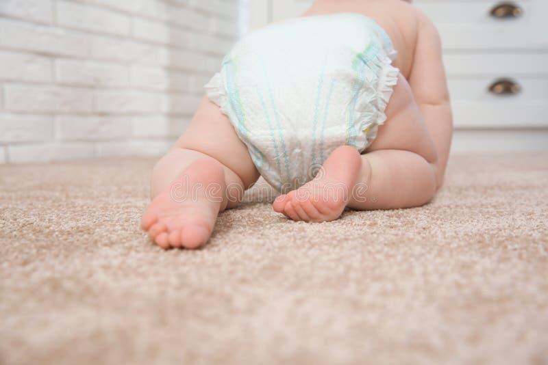 Nettes kleines Baby, das zuhause auf Teppich kriecht stockbild