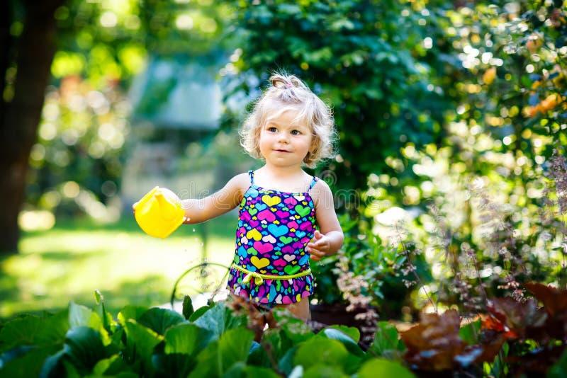 Nettes kleines Baby in den bunten Badeanzugbewässerungsanlagen und Blühen blüht im inländischen Garten am heißen Sommertag lizenzfreie stockfotografie