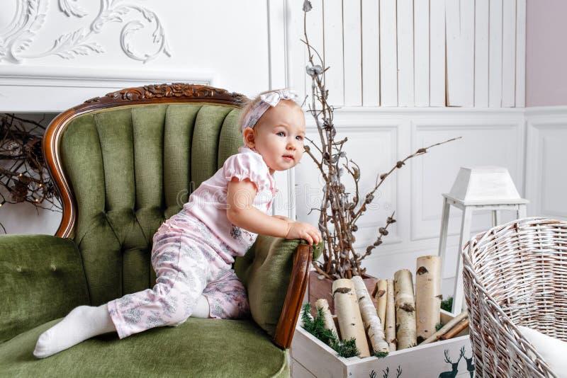 Nettes kleines Baby in den Weinlesestuhl- und -weihnachtsgeschenken Kleines Kind, das Spaß nahe Weihnachtsbaum im Wohnzimmer hat stockbilder