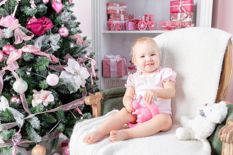 Nettes kleines Baby in den Weinlesestuhl- und -weihnachtsgeschenken Kleines Kind, das Spaß nahe Weihnachtsbaum im Wohnzimmer hat stockfoto