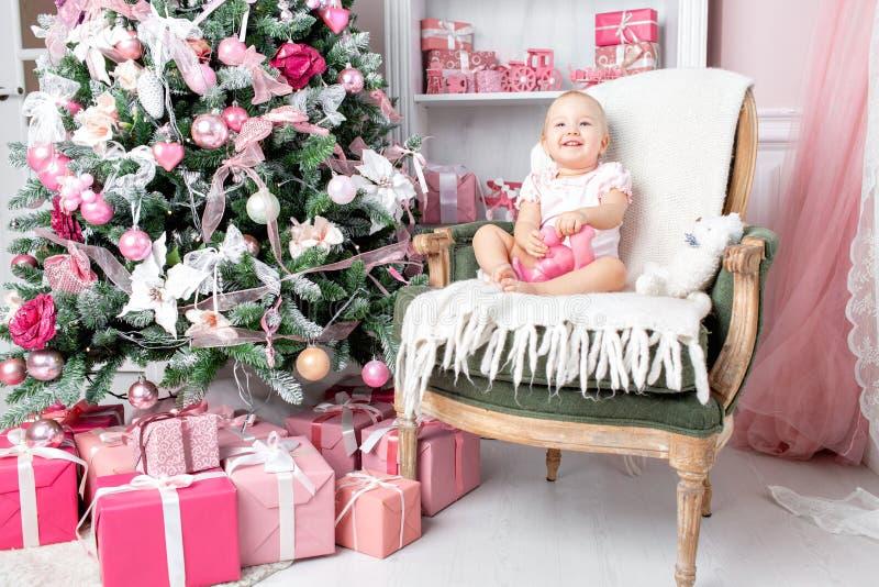 Nettes kleines Baby in den Weinlesestuhl- und -weihnachtsgeschenken Kleines Kind, das Spaß nahe Weihnachtsbaum im Wohnzimmer hat lizenzfreie stockfotografie