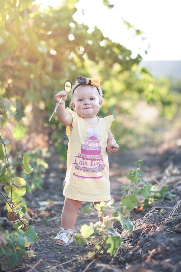 Nettes kleines Baby im gelben Kleid, das auf dem Gebiet von g steht lizenzfreie stockfotografie