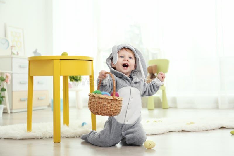 Nettes kleines Baby im Häschenkostüm, das mit Ostereiern spielt lizenzfreie stockfotografie