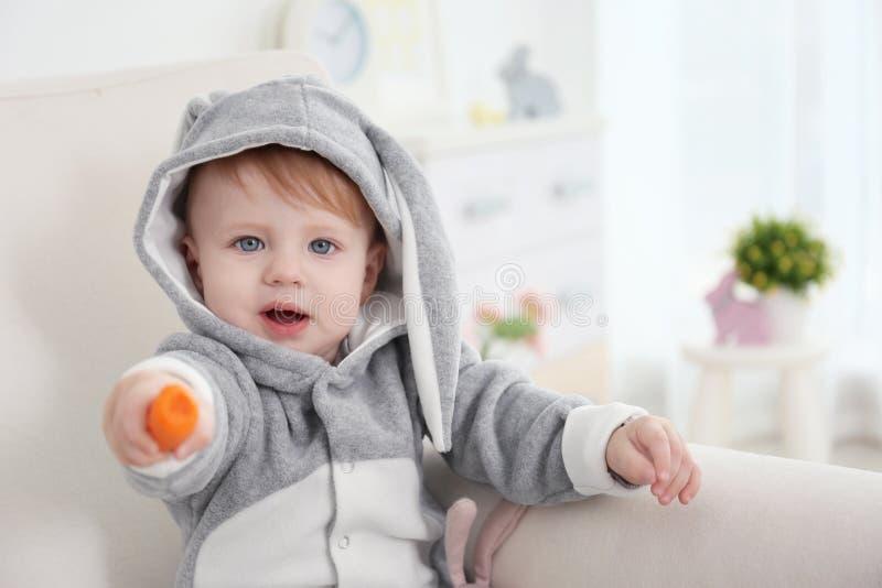 Nettes kleines Baby im Häschenkostüm mit Karotte stockfoto
