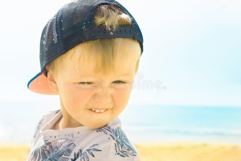 Nettes kleines Baby-Kleinkind-lächelndes lachendes Schielen auf Strand-anziehenden Seifenblasen Echte authentische Gefühle Helles stockfoto