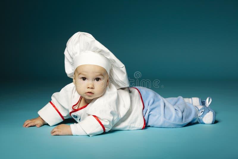Nettes kleines Baby mit Chefhut stockfotografie