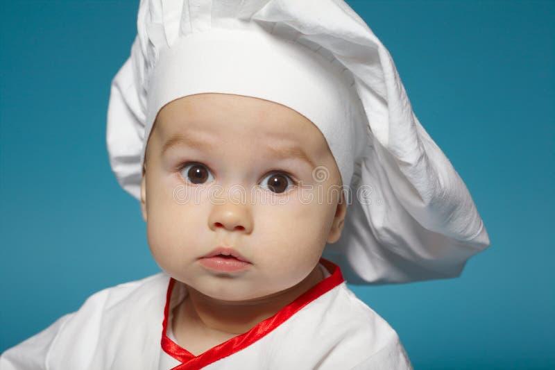 Nettes kleines Baby mit Chefhut stockfotos