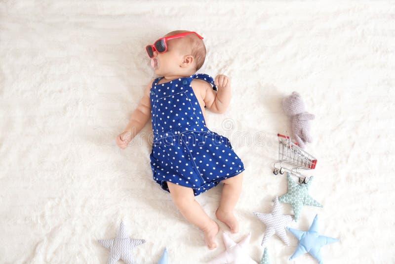Nettes kleines Baby mit der Sonnenbrille und Spielwaren, die auf Bett, Draufsicht liegen stockfotografie