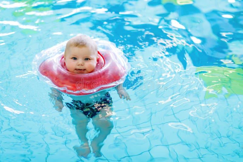 Nettes kleines Babykind, das lernt, mit Schwimmring in einem Hallenbad zu schwimmen lizenzfreie stockfotografie