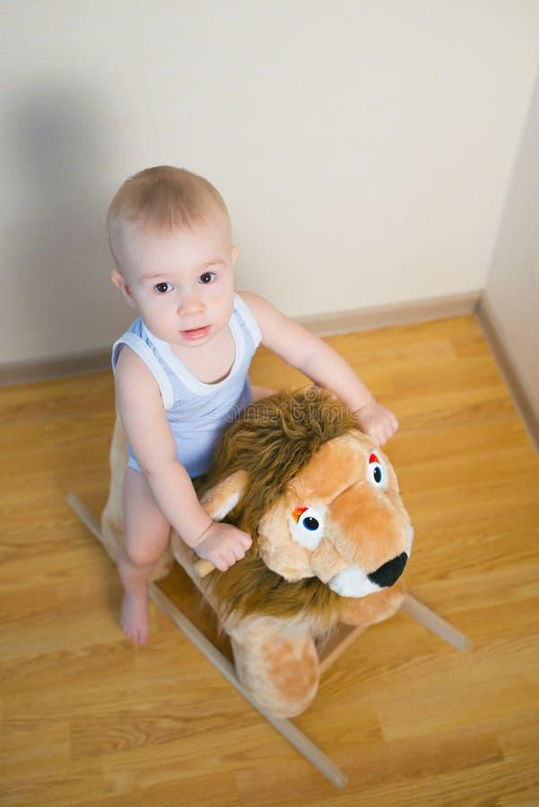 Nettes kleines Babyreiten auf dem Löwespielzeug Glückliche Kindergefühle lizenzfreies stockfoto