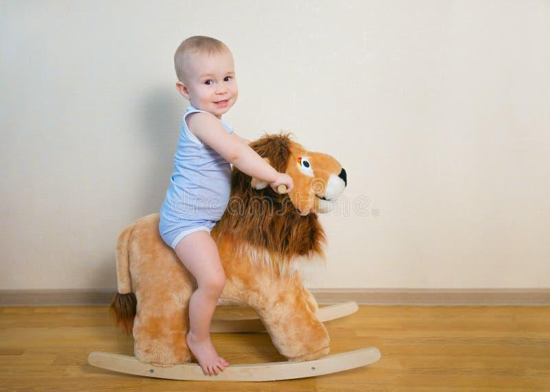 Nettes kleines Babyreiten auf dem Löwespielzeug Glückliche Kindergefühle stockfotos