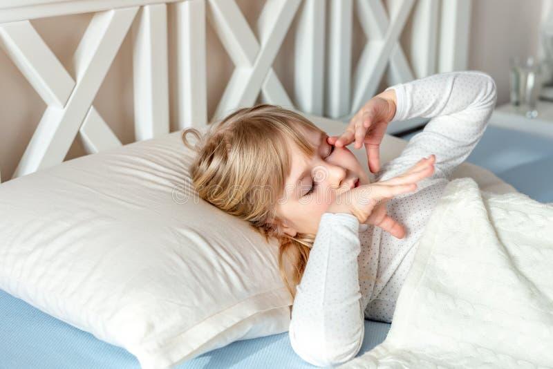 Nettes kleines blondes kaukasisches Mädchen, das am Bett am Morgen weckt Kind wachen früh auf, um zur Schule zu gehen Ausdehnen u stockfotografie