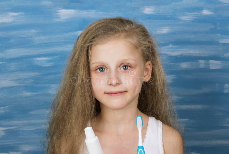 Nettes kleines blondes Mädchen in einem T-Shirt, das ihre Zähne im Badezimmer putzt lizenzfreie stockfotografie